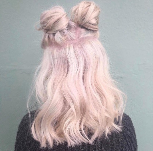 back shot of a woman with medium length pink hair in two space buns half up hair