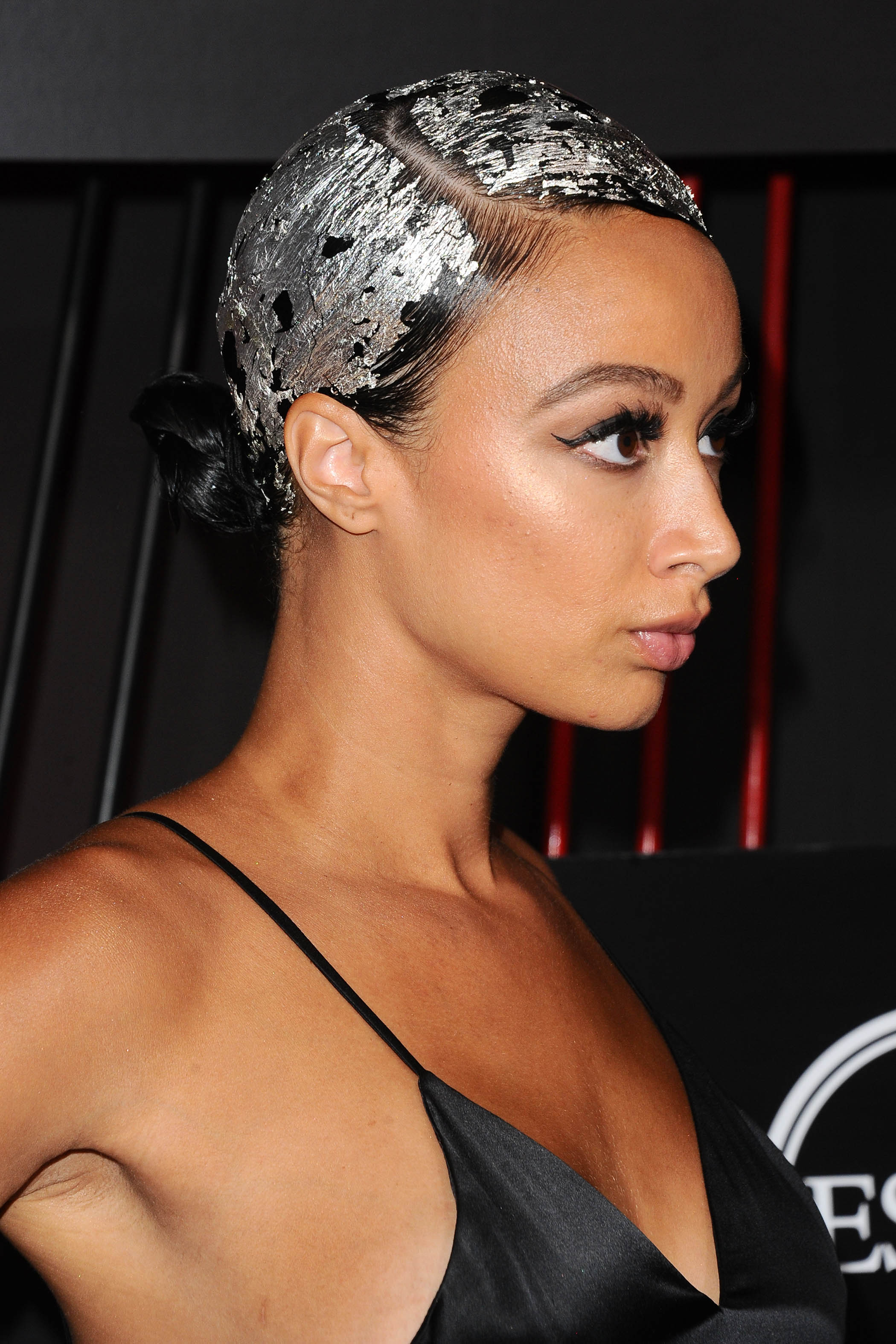 prom updos: side shot of draya michele with sleek hairstyle with metallic foling in it at the espys party