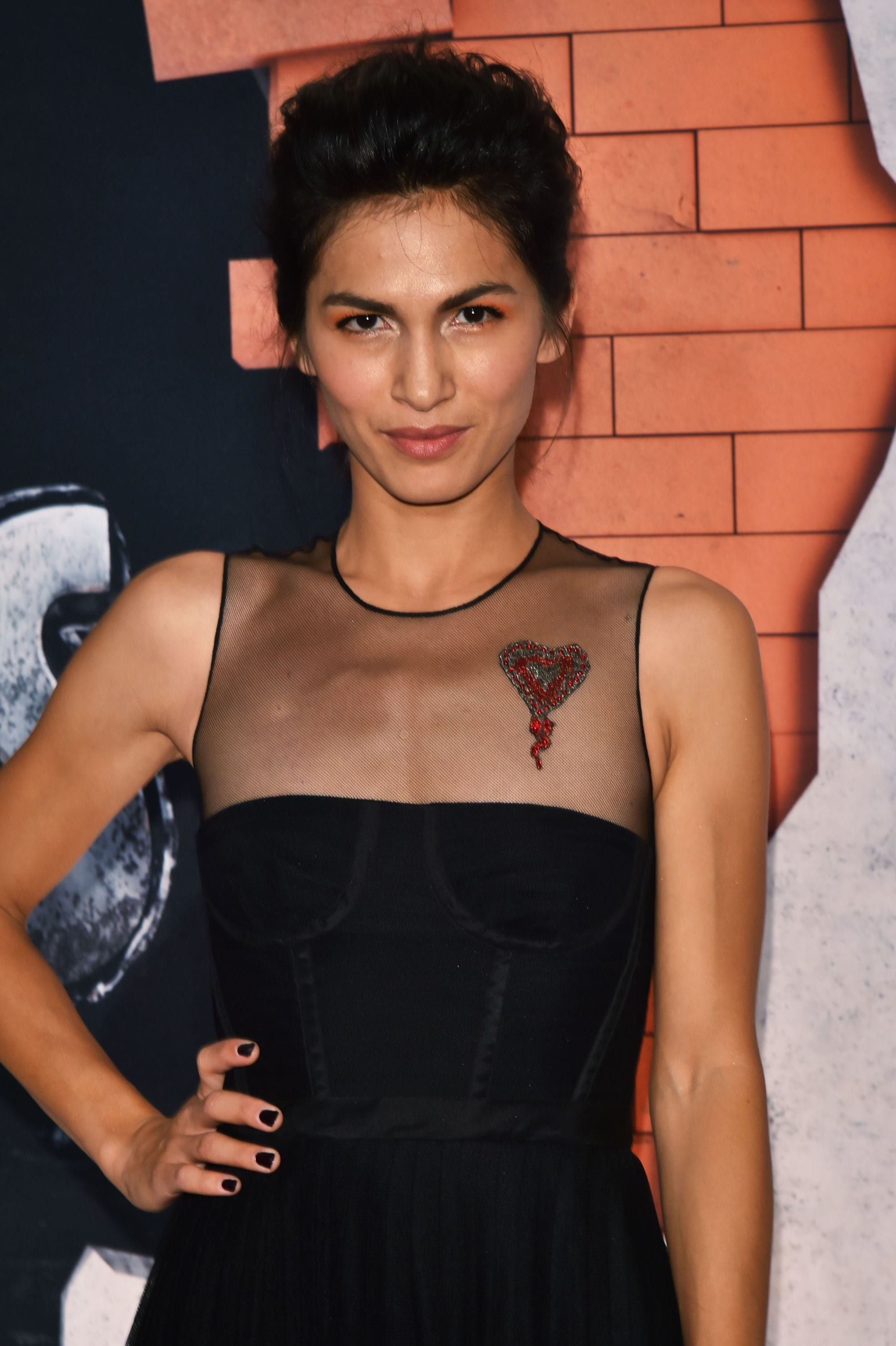 Elodie Yung wears her dark tresses in a textured bouffant swept back updo worn with black dress with sheer detailing