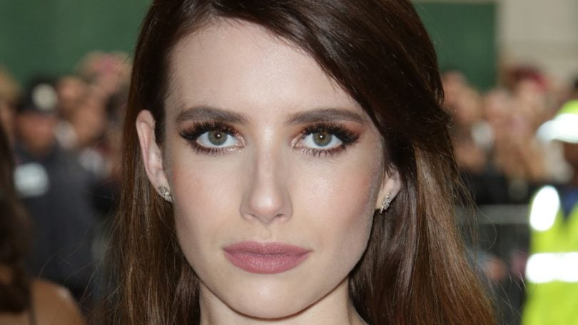 emma roberts with long brunette hair in a pink dress