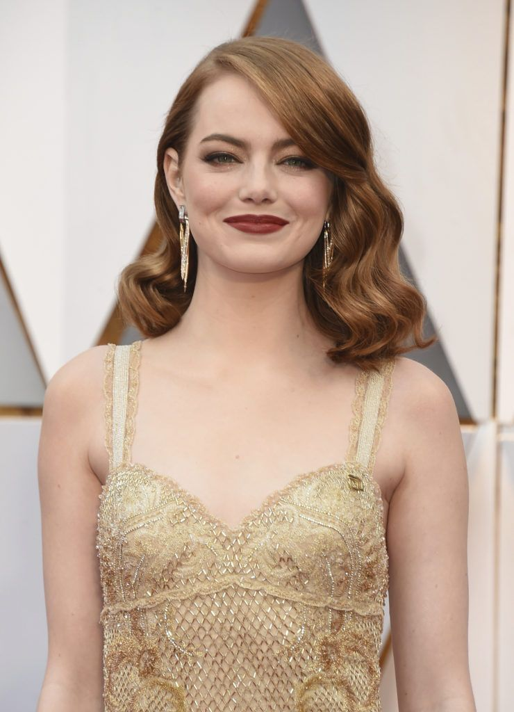 prom hairstyles for medium hair: emma stone copper hair in waves styled in a side parting on the red carpet