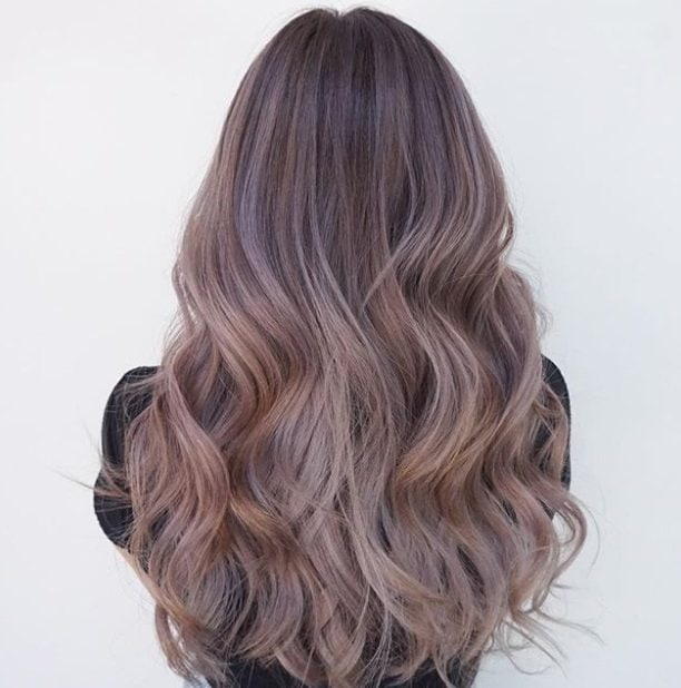 summer hair colour ideas: back shot of woman with lavender sombre hair at a salon