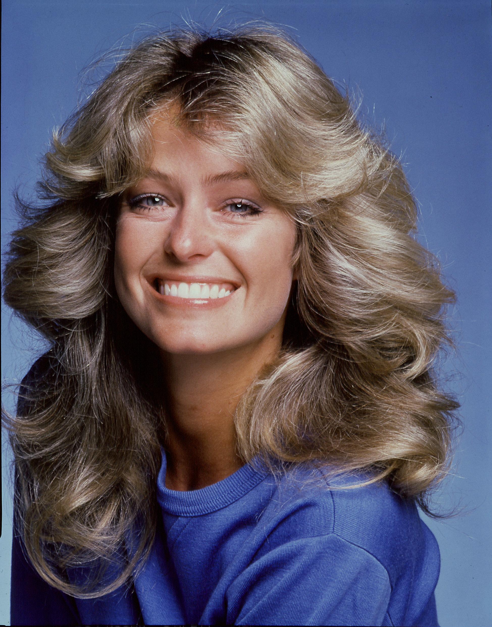 70s hairstyles: Farrah Fawcett long golden blonde 70s flipped out waves wearing a blue top