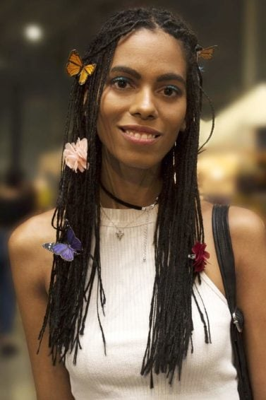 Model with long box braids with colourful butterflies places in hair from Afropunk