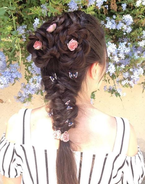 Brown long hair in flower braid style and french braid with pink flowers inserted into the braids