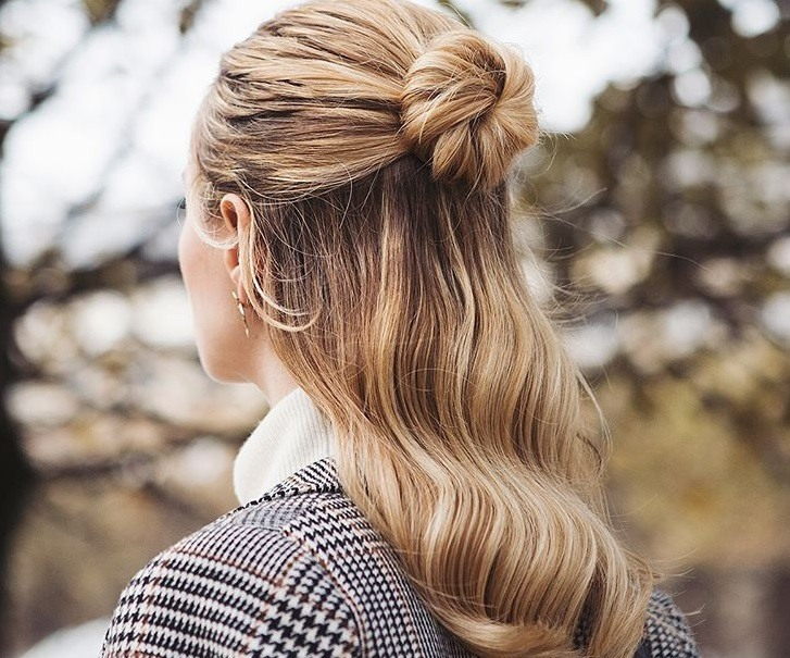 down prom hair ideas: close up shot of woman with bronde sleek half-up, half-down bun hairstyle, wearing checked blazer and posing outside