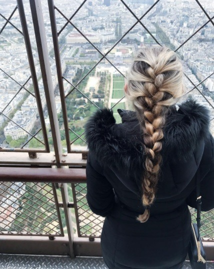 woman with long blonde hair looking out from the eiffel tower with her hair in a