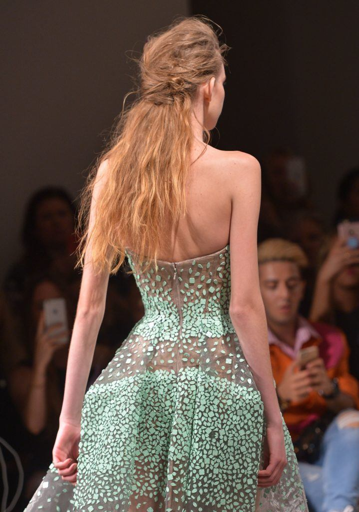 backshot of model at zac posen with half up french twist hairstyle