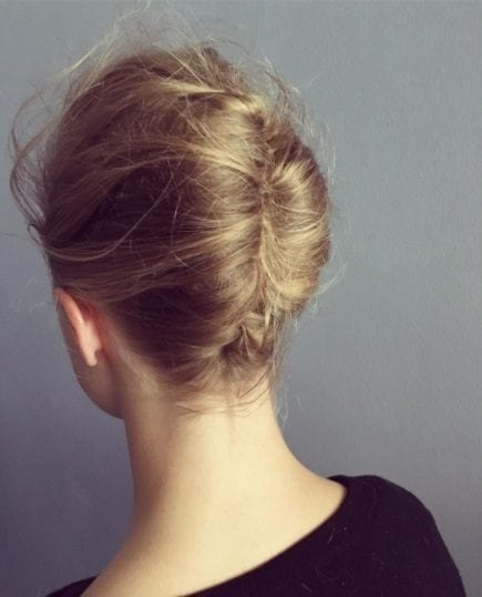 back view of a blonde woman with a french twist updo hairstyle
