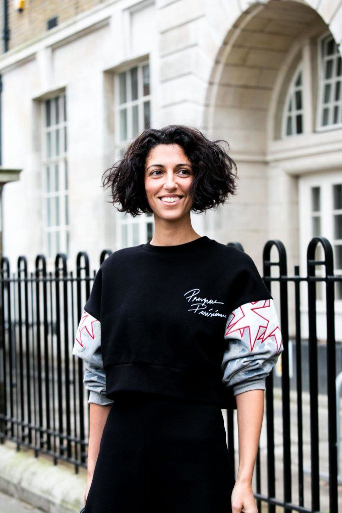 streetstyle photo of a brunette woman with frizzy bob hair