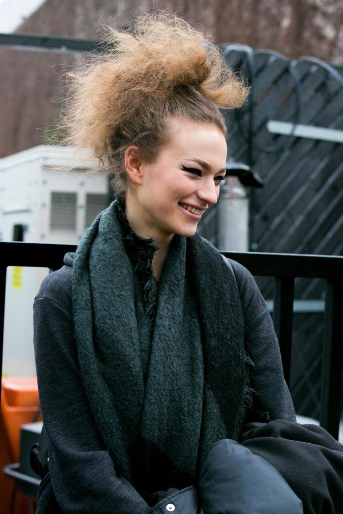 streetstyle image of a model with brunette frizzy hair in an updo