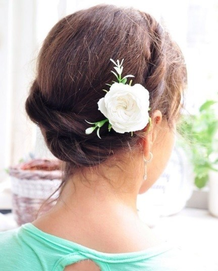 back view of a woman with brunette hair in a milkmaid twist hairstyle with a pink flower hair accessory