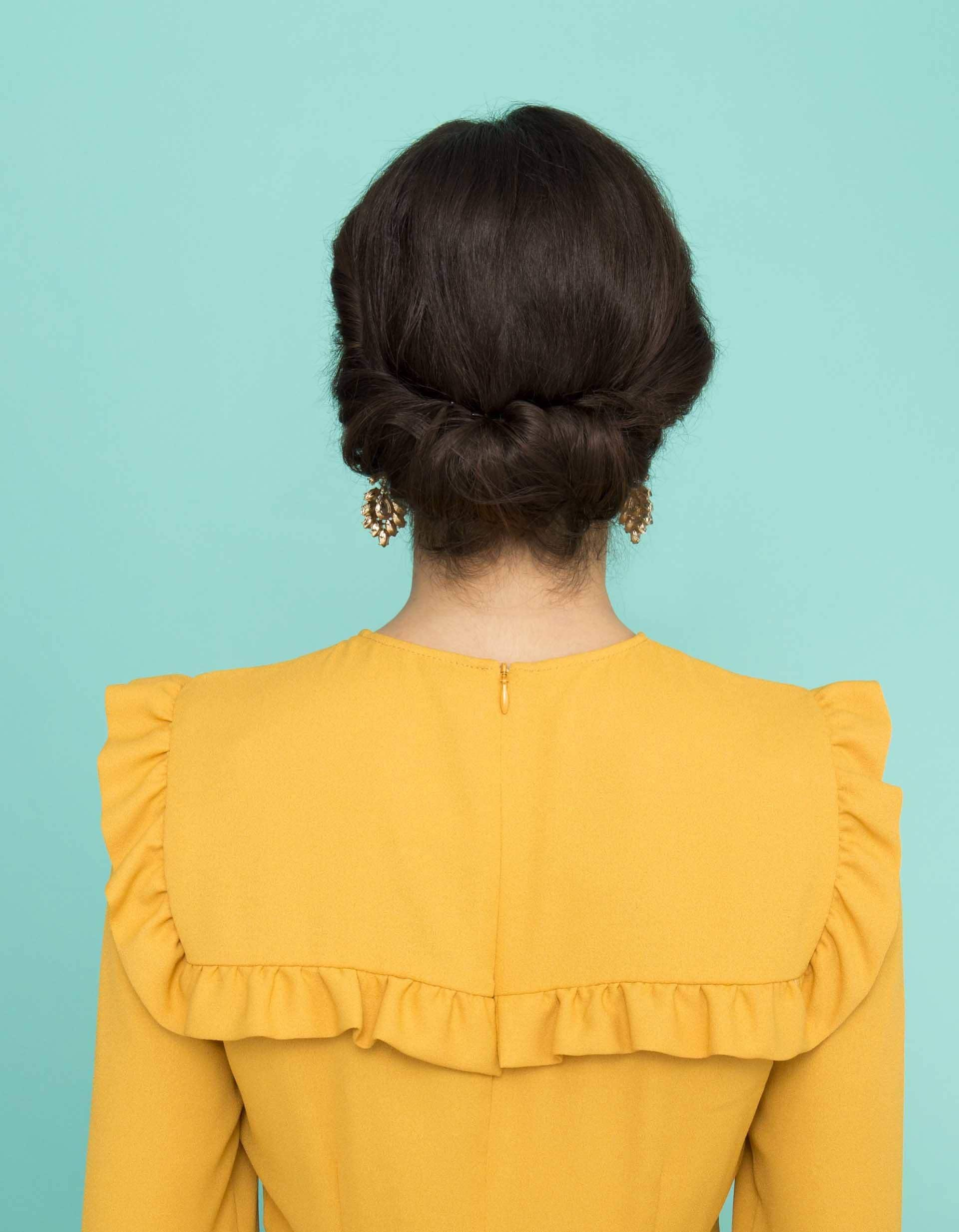 prom hairstyles for medium hair: dark brown haired model showing off gibson tuck hairstyle from behind while wearing bright yellow dress
