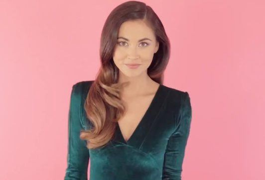 still shot of model with old hollywood waves hairstyle, wearing emerald green dress posing
