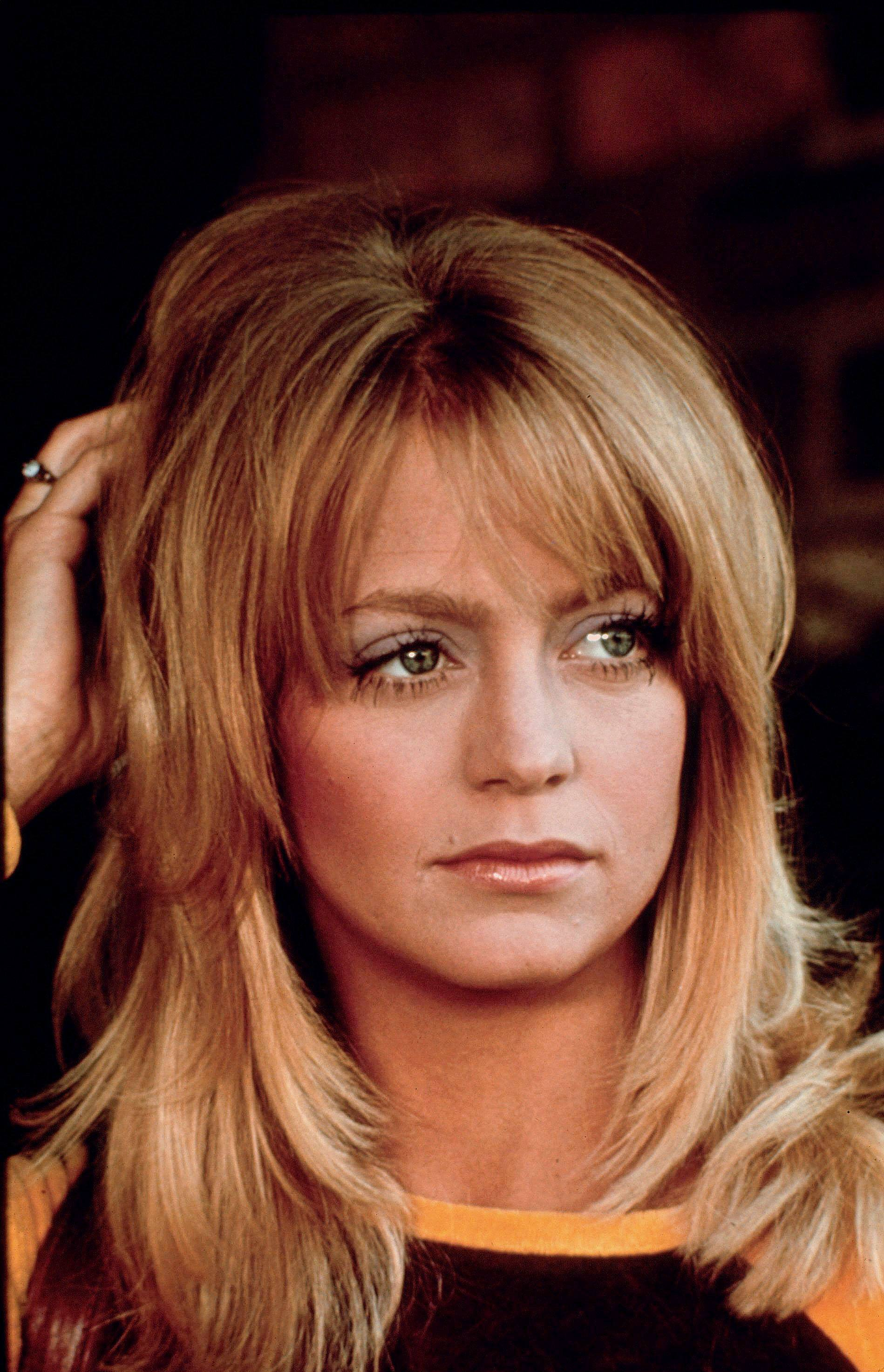 70S hairstyles: Goldie Hawn medium straight golden blonde hair with sweeping bangs