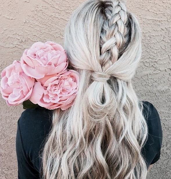 down prom hairstyles: close up shot of a woman with platinum blonde wavy hair, fashioned into a unicorn braid and a half-up, half-down looped ponytail, holding flowers and posing against a white background