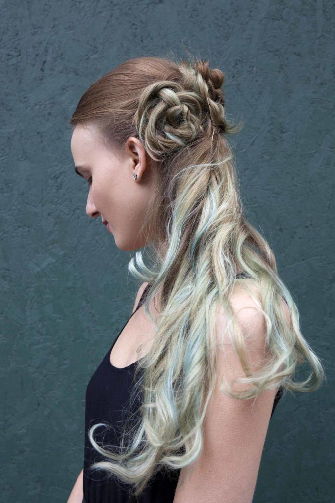 down prom hairstyles: close up shot of a model with brown hair with mint green ombre, with her hair styled up into a half-up Celtic buns, wearing black and posing against a black backdrop