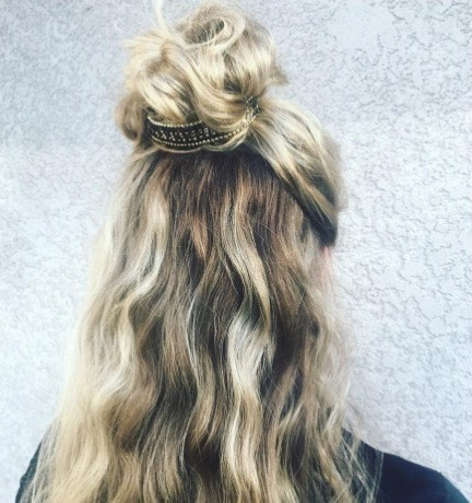 blonde woman with long wavy hair in a half up bun with a cuff detail