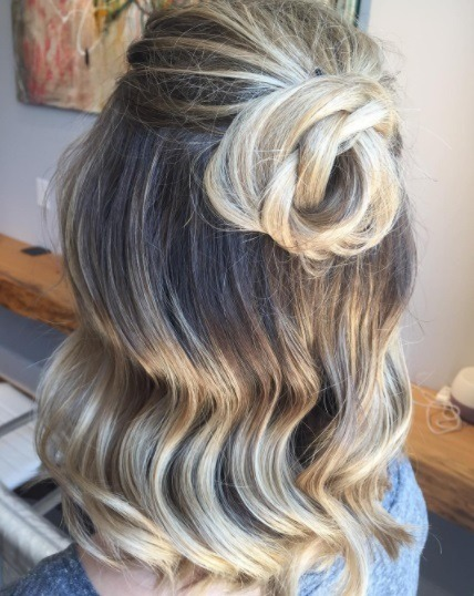 woman with light blonde ombre curled hair in a knotted half up bun