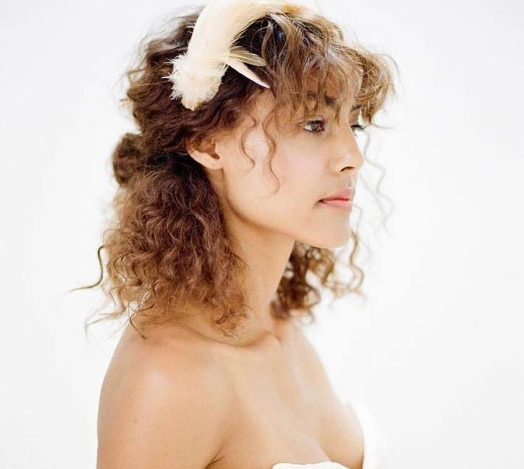 down prom hairstyles: close up shot of woman with caramel brown curls styled into a half-up, half-down hairstyle, complete with a pink headband