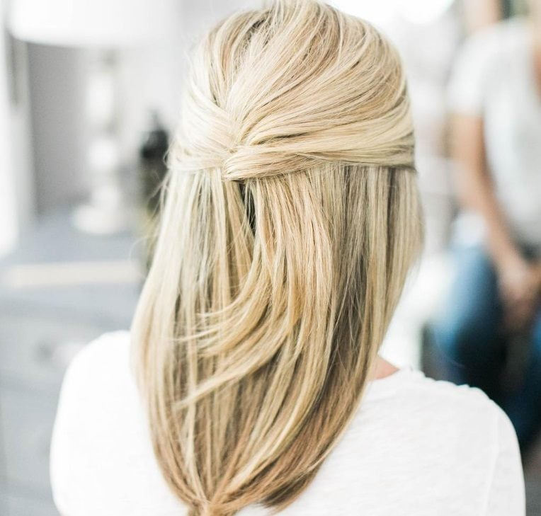 half-up, half-down prom hairstyles: close up shot of a woman with blonde medium length hair, fashioned into half-up french twist