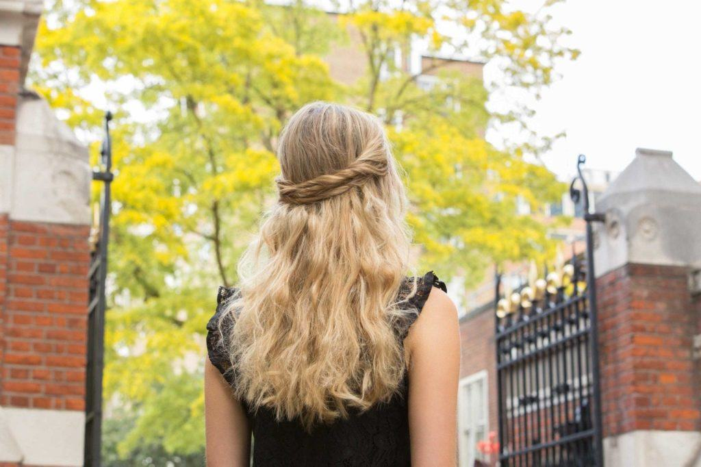 down prom hair ideas: close up back shot of a woman with golden blonde wavy hair fashioned into a half-up, half-down layered twist hairstyle, wearing black shirt and posing outside