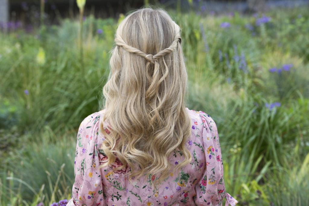down prom hairstyles: close up back shot of a woman with ash blonde hair, wearing a half-up, half-down knotted hairstyle, wearing a pink floral dress and posing outside