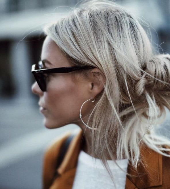 side view of a woman with silver blonde hair in a loose bun wearing sunglasses