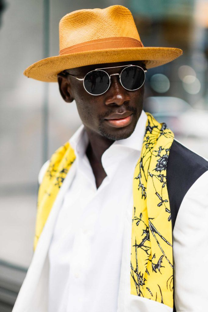 easy hairstyles for guys: street style man with hat and sunglasses with white shirt and backpack