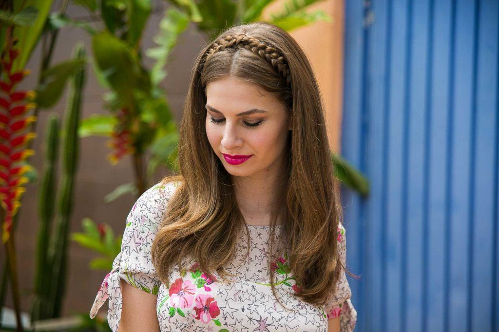 braided down prom hairstyles: close up shot of model with medium brown hair styled into a loose waves and a headband braid, wearing floral top and posing outside