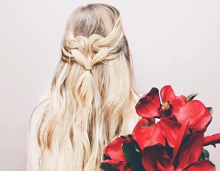 down prom hairstyles: back shot of woman with platinum blonde hair styled into a half-up heart loop hairstyle, holding flowers and posing against a white background