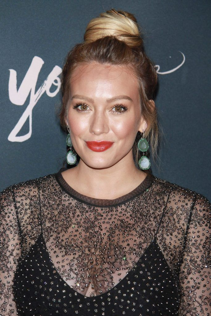 prom updos: hilary duff on the red carpet with her blonde hair in a high ballerina bun wearing a black lace outfit