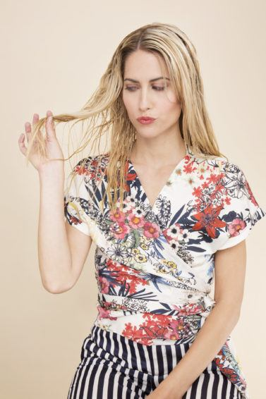 blonde model wearing a floral wrap blouse and striped trousers with wet hair
