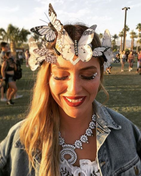 girl with medium long straight hair wearing a white butterfly headband crown at Coachella 2017 festival.
