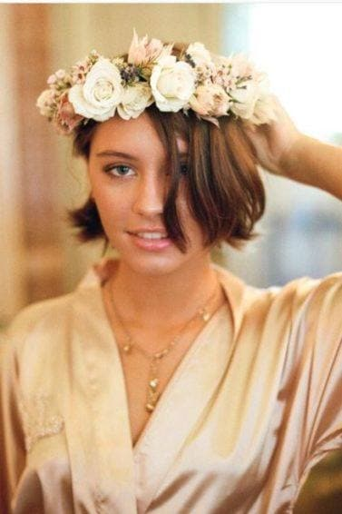 Front view of Iris Law with bob length medium tones brown hair with flower crown headband