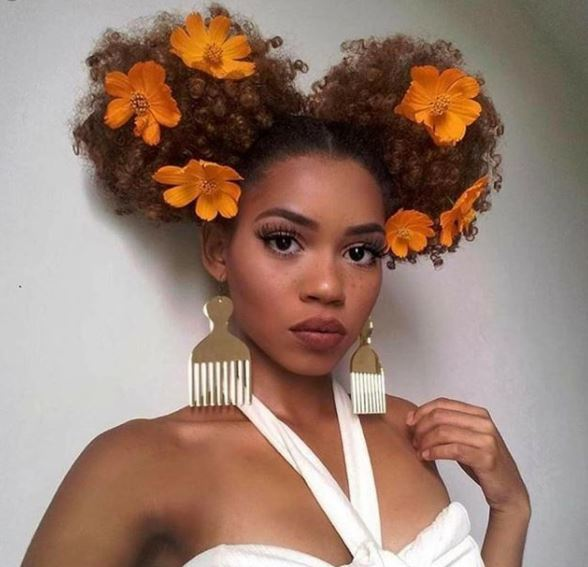 golden brown curly space bun puffs with orange floral accessories in selfie picture