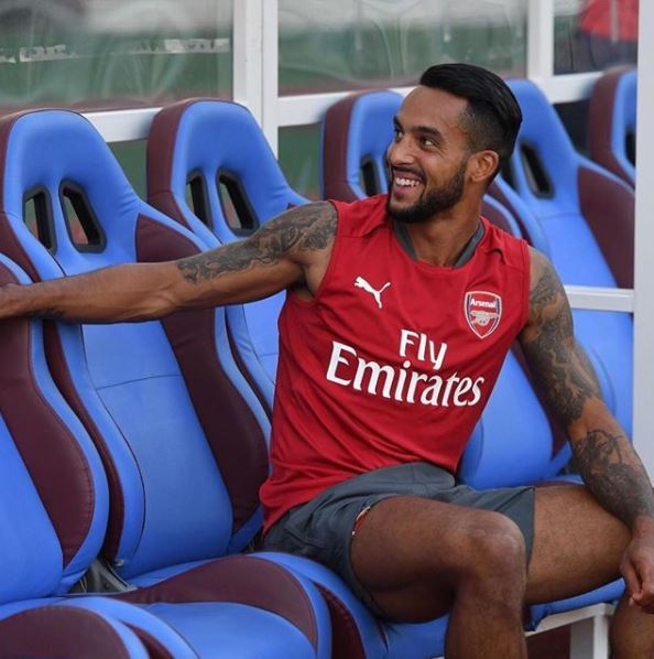 Theo Walcott dark black hair in slick back with faded sides wearing Arsenal vest