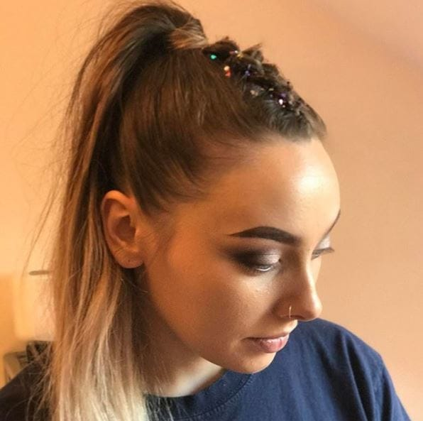 Dark blonde balayage hair with braids down the centre and up itno high ponytail with glitter sprinkled down the braid