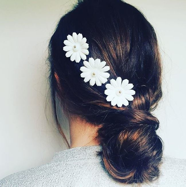 back view of medium brown hair in loose twisted low bun with white floral accessories