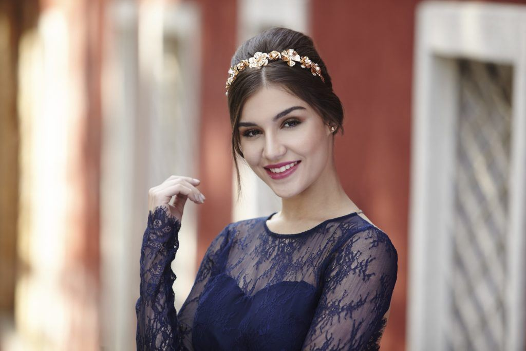 prom hairstyles for medium hair: model with dark brown straight hair styled in a beehive bouffant updo with gold floral headband wearing a navy lace dress