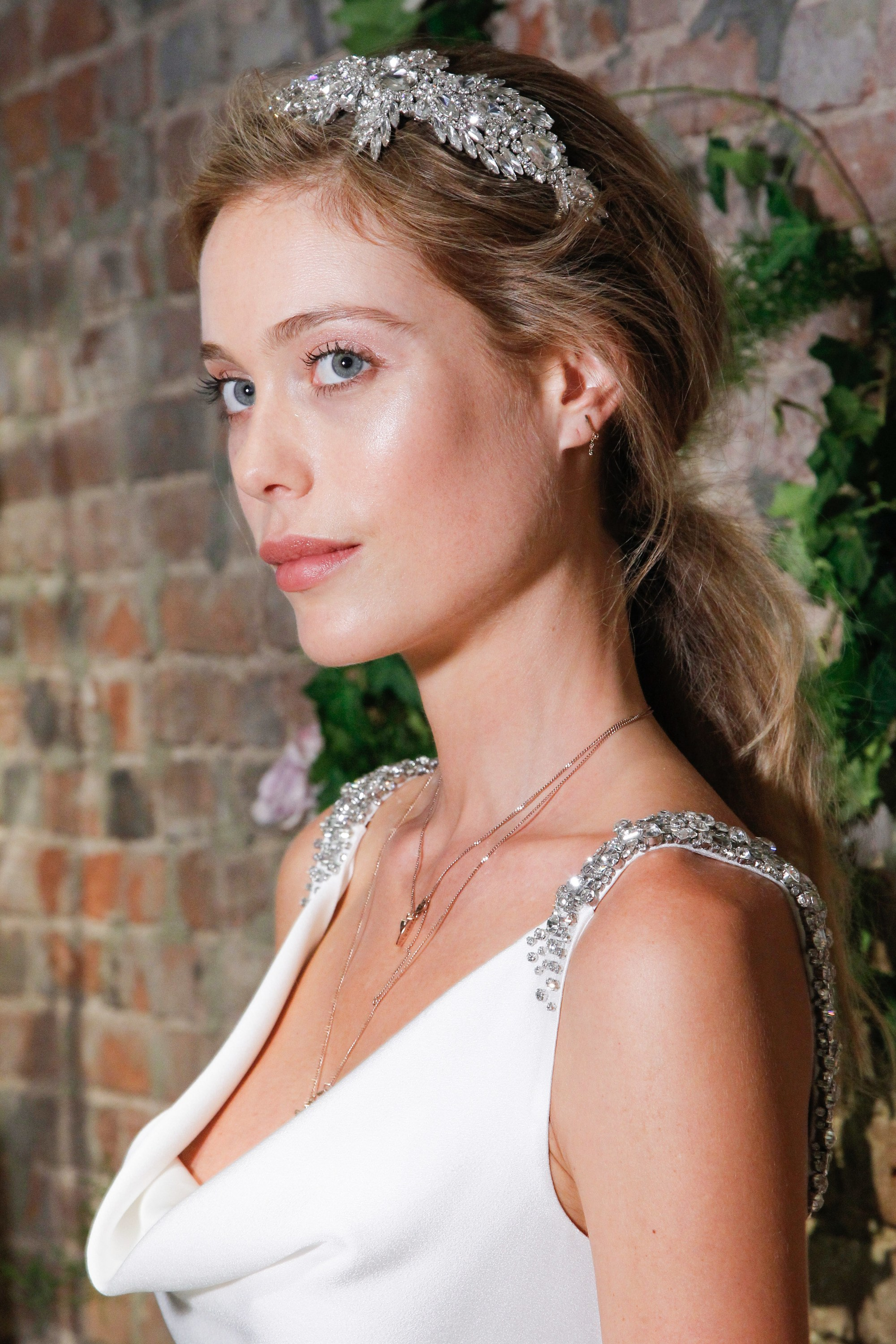 simple wedding hairstyles: model with low ponytail with headband at jenny packham