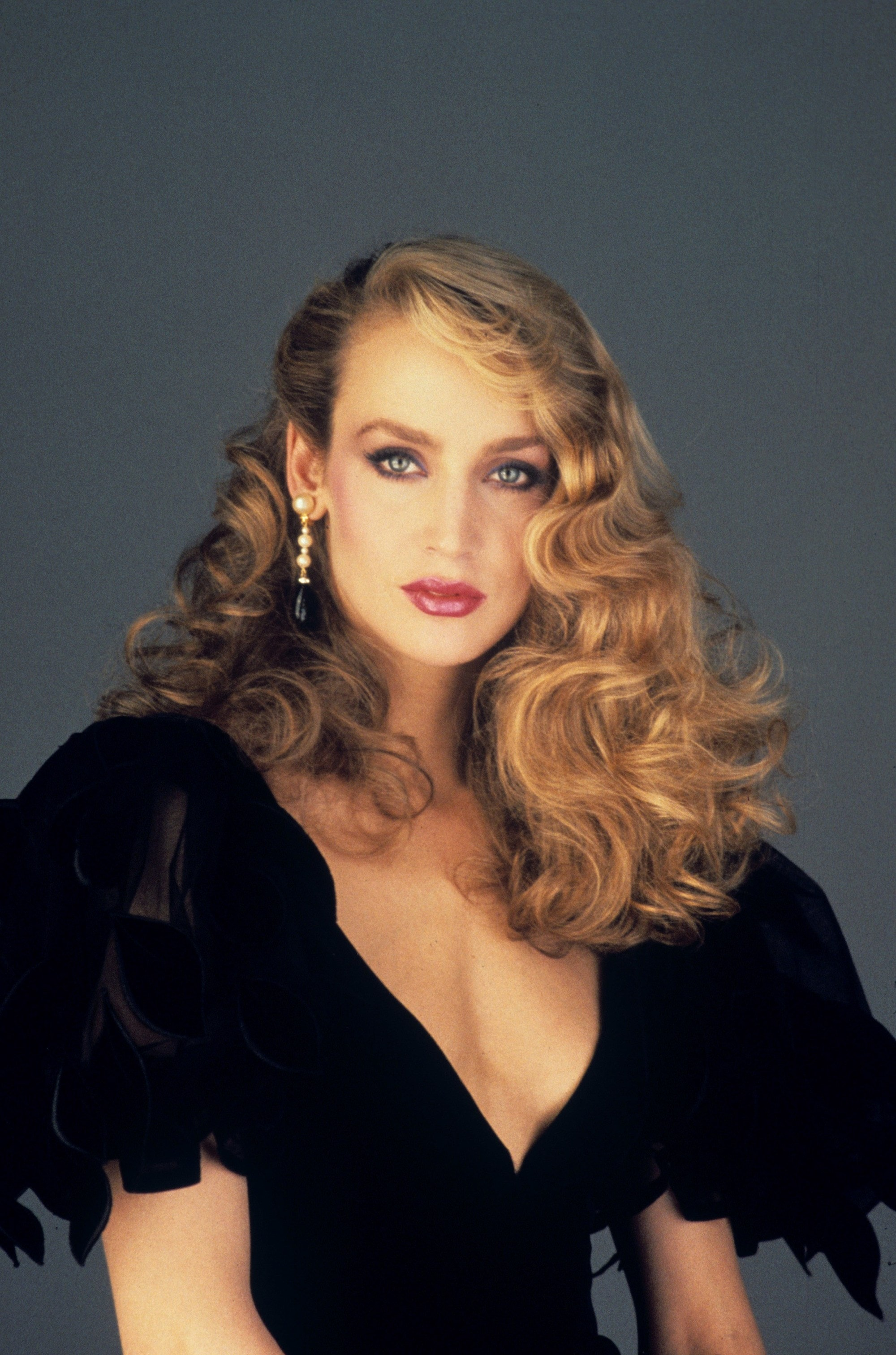 70s hairstyles: Jerry Hall long curly golden blonde hair swept over one shoulder wearing big sleeved black dress