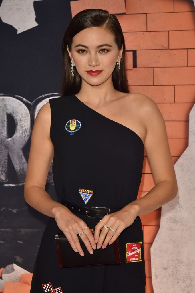 Jessica Henwick wears her dark tresses in a side parting and swept back in a smooth finish the look is finished with a one shoulder black dress