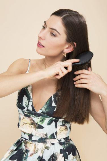 Keratin shampoo: Model brushing her long straight brown hair wearing a floral outfit.