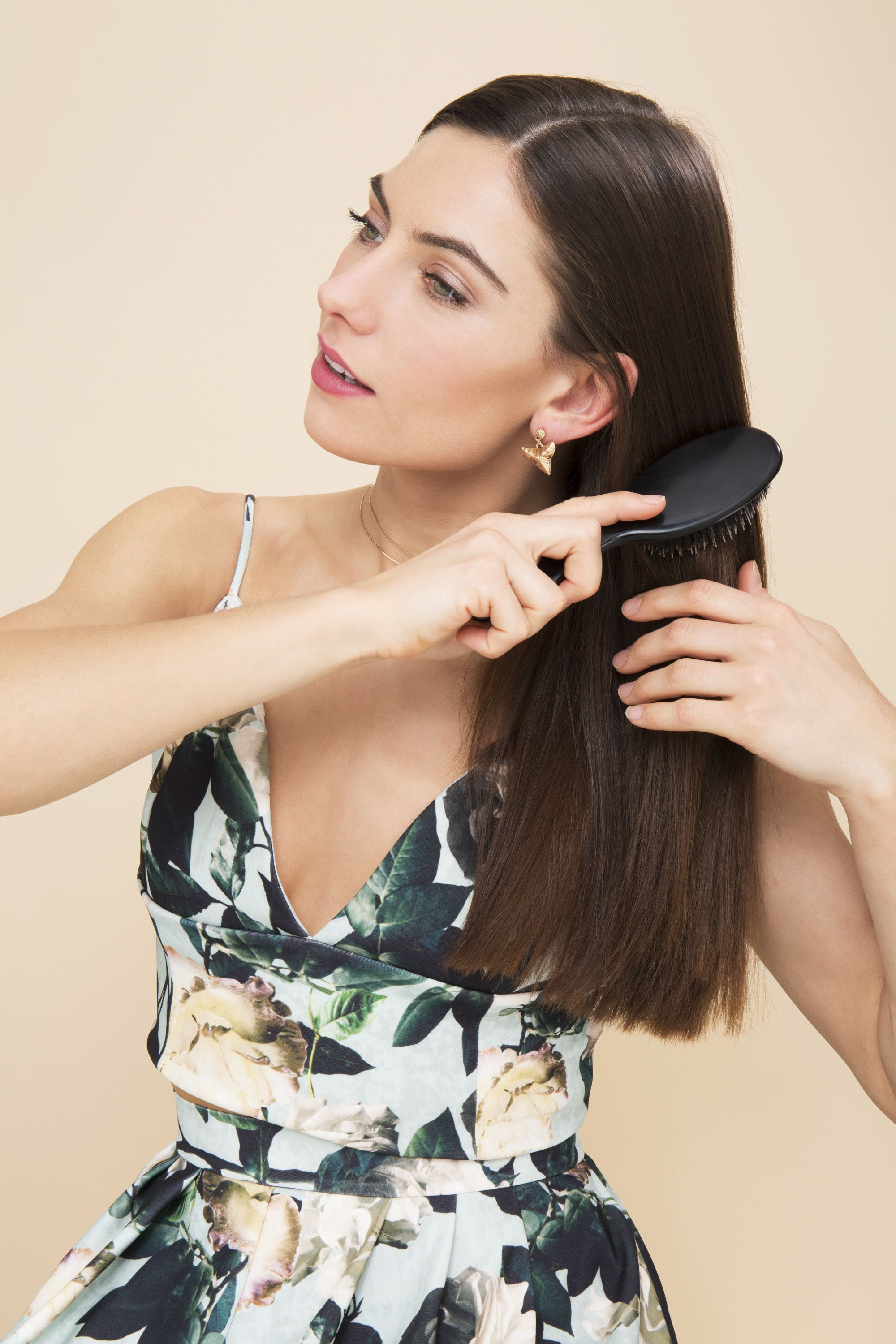 Keratin shampoo and conditioner guide: model brushing her hair after using keratin oil wearing floral dress