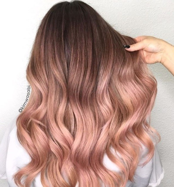 back shot of woman with long wavy peach coloured ombre hair at a salon