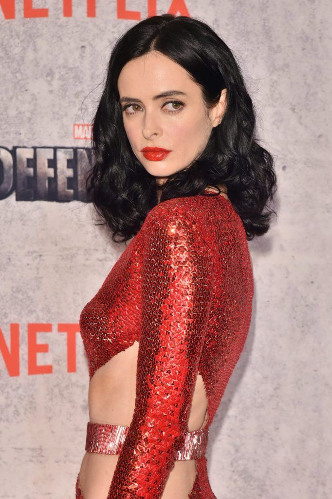 Krysten Ritter wears her black mid length tresses in loose curls hairstyle and bol red lipstick and red sequin cut out dress