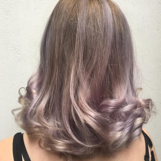 back shot of a woman with brown hair with lilac balayage highlights