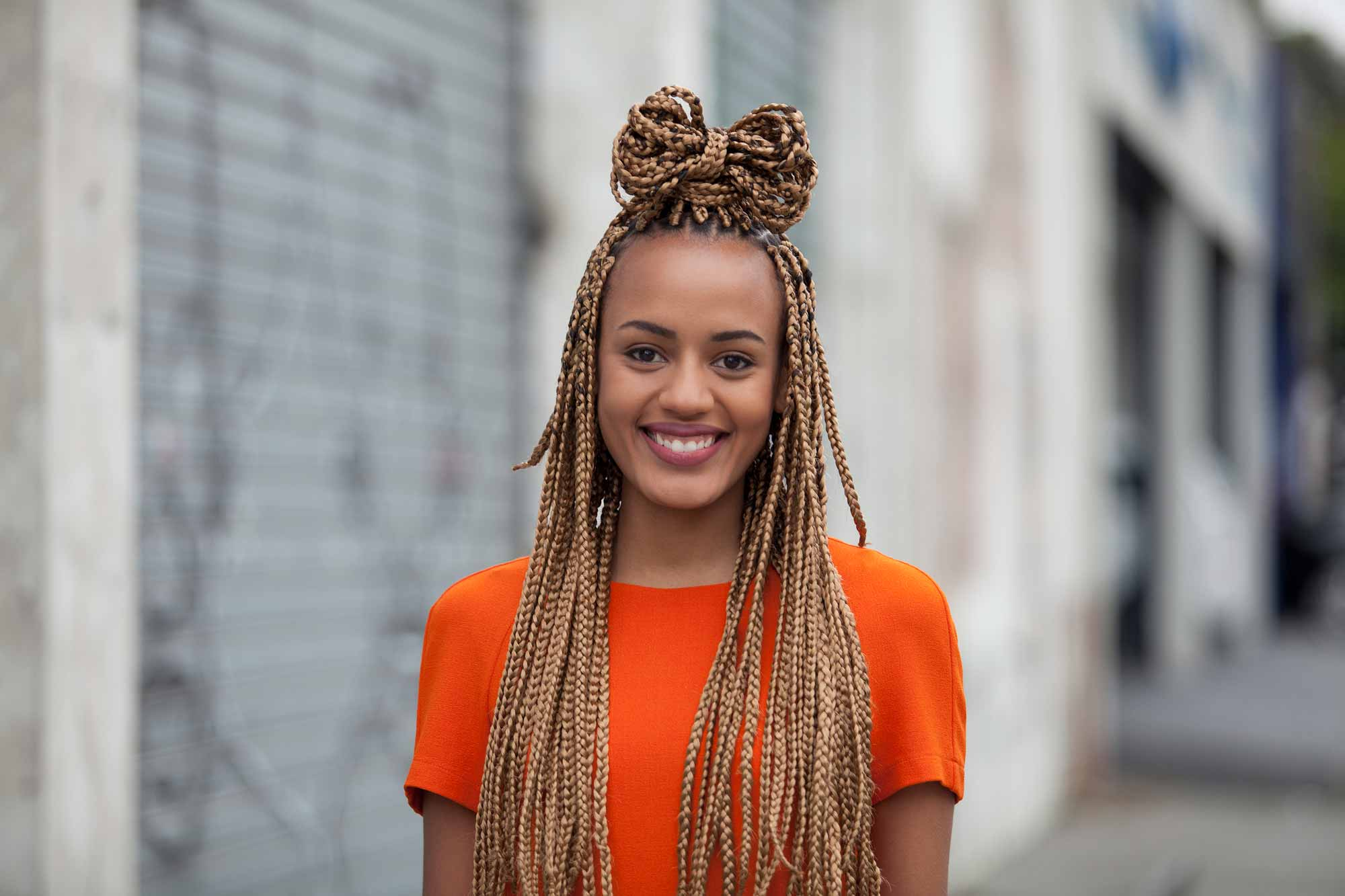 Long box braids hairstyles: Smiling model with long golden box braids in a half-up bow hairstyle, wearing an orange top