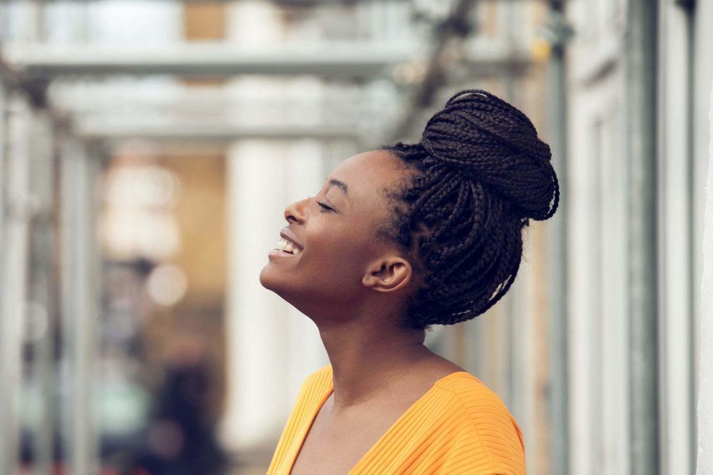Long box braids hairstyles: Smiling side profile of a woman with long dark brown box braids in a high bun, wearing a yellow top